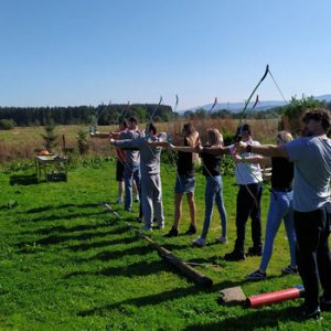 people in line wiht bow and arrows in countryside