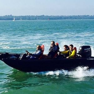 black boat in water with people in safety equipment