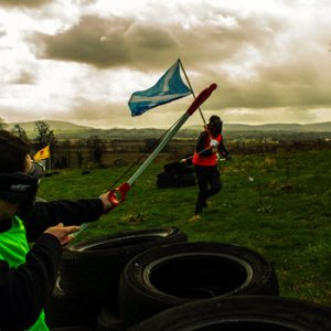 people running with scottish flag in combat gear in countryside